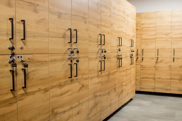 Szafki drewniane, z metalowymi zamkami. klasyczna szatnia z drewna i ławka.