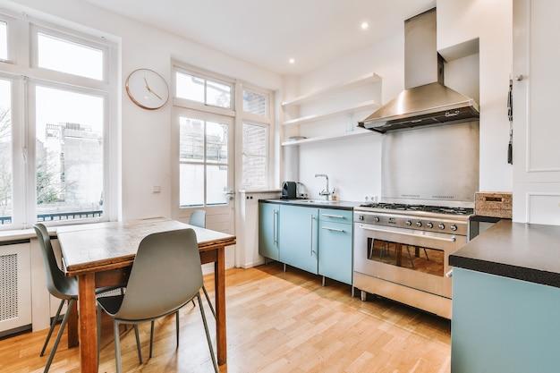 Szafki i kuchenka gazowa z okapem znajdują się obok stołu z krzesłami przy oknach w widnej kuchni w domu