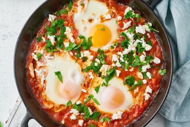 Szakszuka, jajka gotowane w sosie z pomidorów, oliwa z oliwek. kuchnia śródziemnomorska.