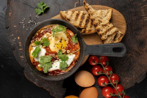 Szakszuka w stylu szefa kuchni. klasyczne izraelskie danie z jajek smażonych w sosie z pomidorów, ostrej papryki, cebuli i przypraw.