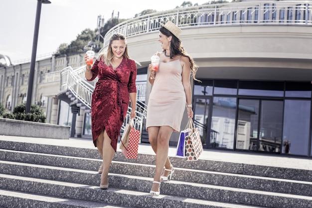 Szał zakupów. zachwycone miłe kobiety schodzące po schodach z lemoniadą