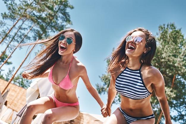 Szaleje, szaleje, dwie atrakcyjne i zabawne młode kobiety w stylowych strojach kąpielowych i okularach przeciwsłonecznych