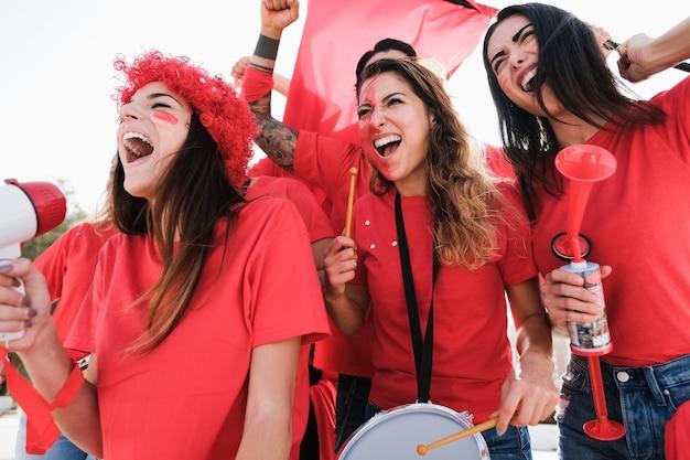Szaleni fani piłki nożnej bawią się na zewnątrz stadionu na mecz piłki nożnej - skup się na twarzy dziewczyny w środku