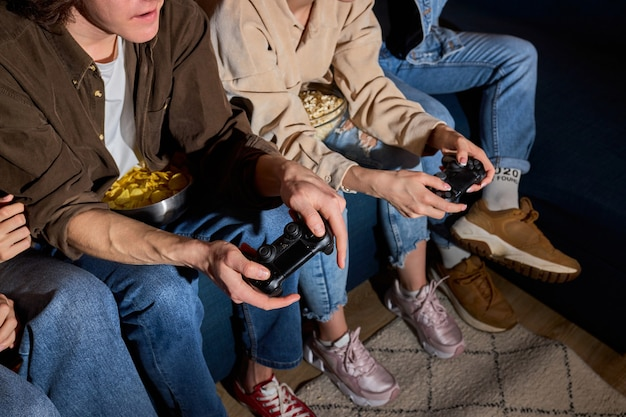 Szaleni młodzi ludzie przyjaciele cieszący się graniem w konsolę do gier wideo, odpoczynek w domu, odpoczynek w domu, w codziennych ubraniach, konsola do gier