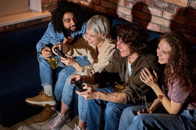 Szaleni młodzi przyjaciele bawią się wieczorem w gry wideo, utrzymuj rywalizację podczas gry, ubrani niedbale