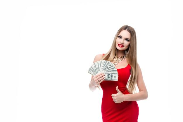 Szalenie piękna młoda kobieta w czerwonej sukience trzymająca dużo banknotów 100-dolarowych i pokazująca kciuki do góry. modna dziewczyna w czerwonej sukni wieczorowej z jasnym makijażem i czerwonymi ustami.