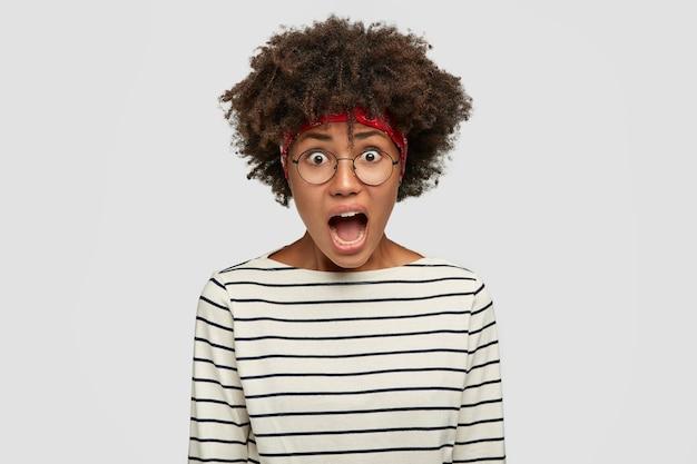 Szalona afroamerykanka krzyczy z zirytowaną miną, ma krzaczaste włosy, ubrana w czarno-biały swobodny sweter w paski, ma opuszczoną szczękę, czuje się niespokojna, odizolowana na białej ścianie