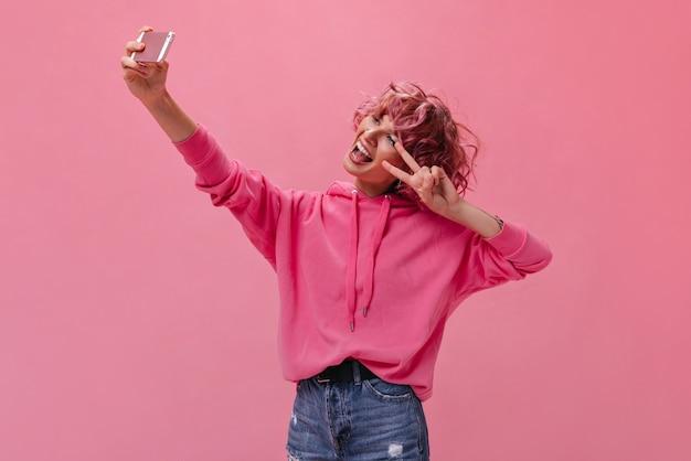 Szalona aktywna kobieta z różowymi włosami robi selfie na białym tle