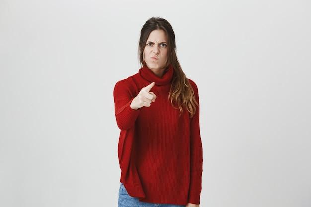 Szalona dziewczyna oskarża kogoś, wskazując kamerą i marszcząc brwi