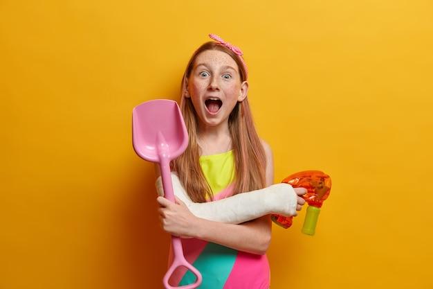 Szalona figlarna rudowłosa dziewczyna trzyma usta otwarte, bawi się pistoletem na wodę w upalny letni dzień, bawi się nad morzem, trzyma plastikową łopatę z piaskiem, nosi strój kąpielowy, lubi zabawne letnie gry z przyjaciółmi
