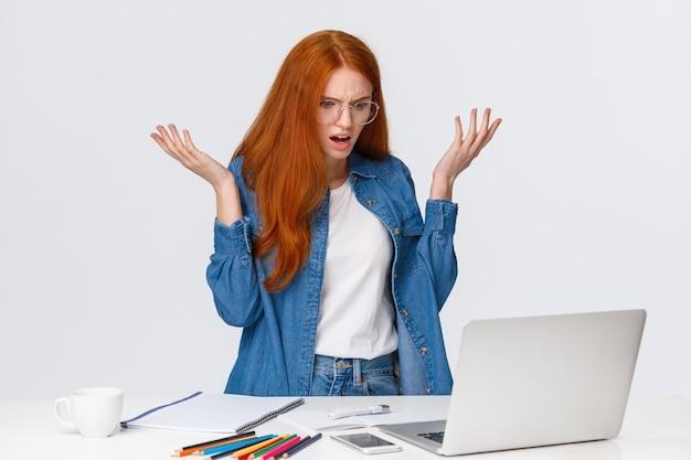 Szalona i zdezorientowana, sfrustrowana ruda dziewczyna mająca problemy z komputerem, pracująca nad ciężkim projektem, podnosząca ręce do góry z konsternacji i irytacji, wzruszająca ramionami, wpatrzona w ekran laptopa