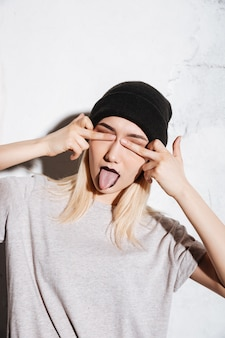Szalona kobieta zakryła oczy środkowymi palcami i pokazała język