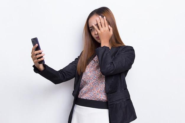 Szalona młoda azjatycka kobieta biznesu korzystająca z telefonu komórkowego na białym tle
