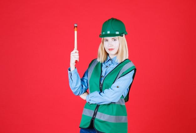 Szalona młoda kobieta budowniczy zielony mundur i hełm trzymający młotek, patrząc poważnie na czerwonej ścianie