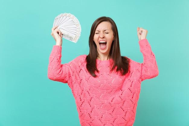 Szalona młoda kobieta w różowym swetrze krzyczy, trzymając mnóstwo banknotów dolarów, gotówki, zaciskając pięść jak zwycięzca na białym tle na niebieskim tle. koncepcja życia ludzi. makieta miejsca na kopię.