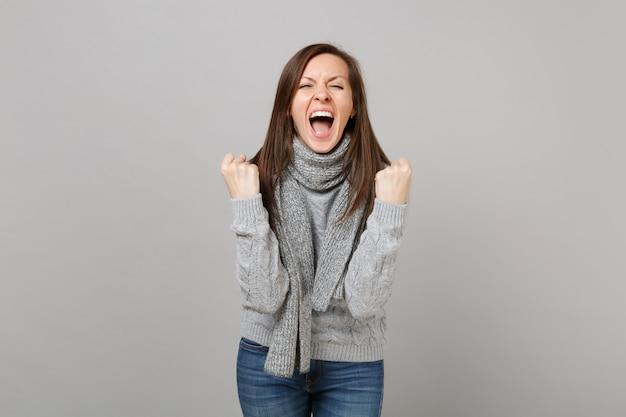 Szalona młoda kobieta w szarym swetrze, szalik krzyczy zaciskając pięści jak zwycięzca na białym tle na szarym tle. zdrowy styl życia moda, szczere emocje ludzi, koncepcja zimnej pory roku. makieta miejsca na kopię.