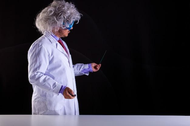 Szalona nauczycielka nauk ścisłych w białym fartuchu z rozczochranymi włosami w śmiesznych okularach trzymająca różdżkę wskazującą na tablicę