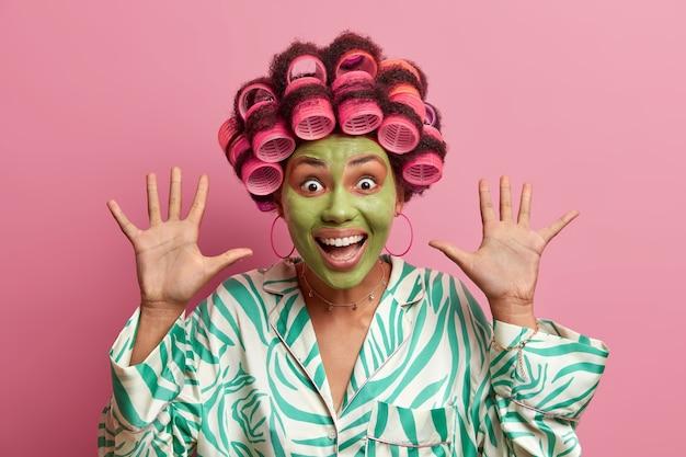 Szalona, podekscytowana, emocjonalna kobieta wygląda z wesołym wyrazem twarzy, trzyma dłonie uniesione, szeroko się uśmiecha, nosi wałki do włosów, zieloną maskę upiększającą, nosi zwykły szlafrok