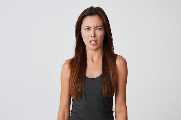 Szalona podrażniona młoda kobieta z długimi włosami wygląda na złą