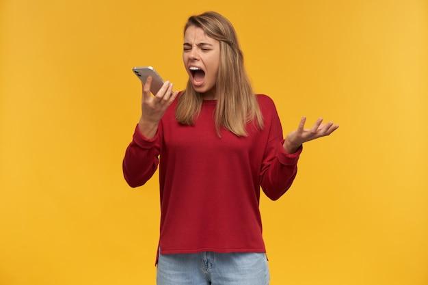 Szalona, rozczarowana dziewczyna trzyma w dłoni telefon komórkowy, patrząc na niego, jakby dzwoniła, otworzyła usta, jakby na kogoś krzyczała
