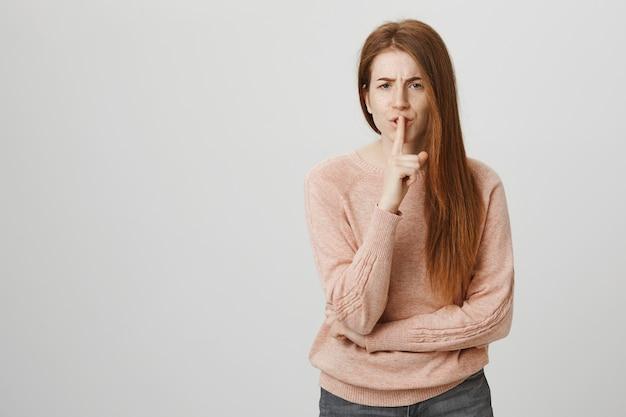 Szalona rudowłosa kobieta z piegami uciszająca się z niespokojnym spojrzeniem