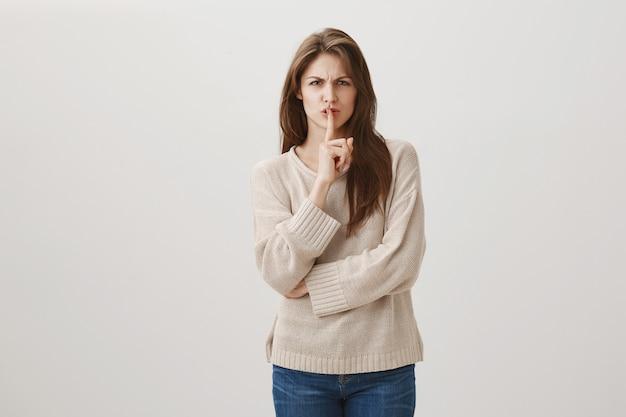 Szalona, skrzywiona kobieta mówi bądź cicho, uciszając osobę