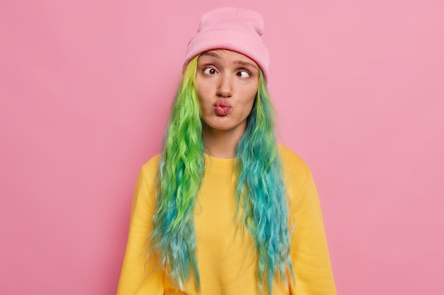 Szalona studentka z kolorowymi włosami bawi się sama niezręczna ekspresja głupcy po całym dniu nauki krzyże oczy wydąża wargi nosi kapelusz i sweter pozuje w różowym studiu