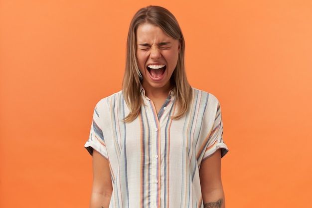 Szalona, szalona młoda kobieta w pasiastej koszuli stoi i krzyczy na białym tle nad pomarańczową ścianą