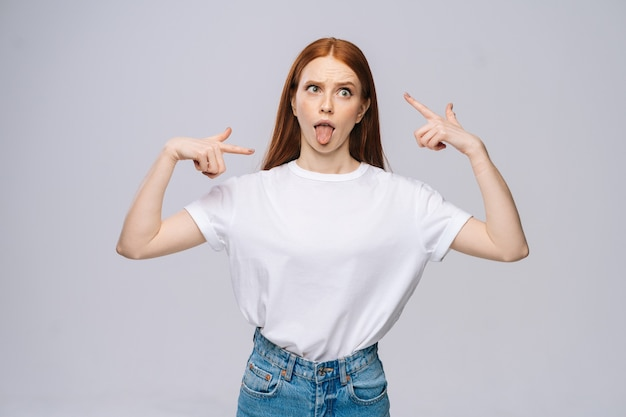 Szalona szczęśliwa młoda kobieta ubrana w koszulkę i dżinsowe spodnie pokazujące język na na białym tle