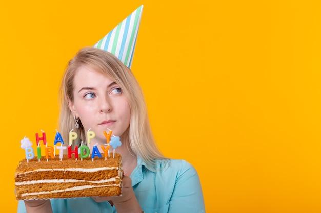 Szalona wesoła młoda kobieta w papierowym gratulacyjnym kapeluszu trzyma ciasta wszystkiego najlepszego z okazji urodzin stojących na