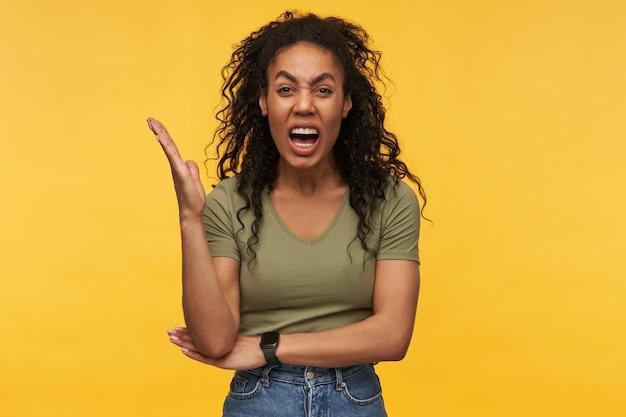Szalona, wściekła młoda kobieta w zwykłych ubraniach trzyma rękę podniesioną i krzyczy na białym tle nad żółtą ścianą