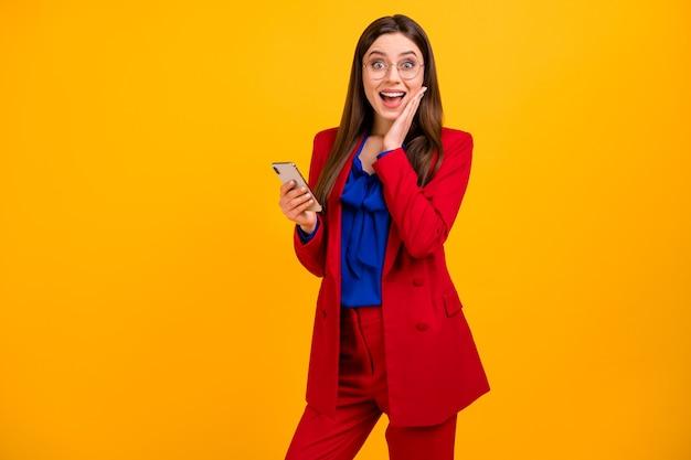 Szalona, zdumiona dziewczyna, uzależniona od freelancera, blogerka używa telefonu komórkowego