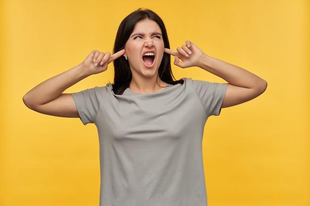 Szalona, zła, brunetka, młoda kobieta w szarej koszulce zamknęła uszy palcami i krzyczała nad żółtą ścianą