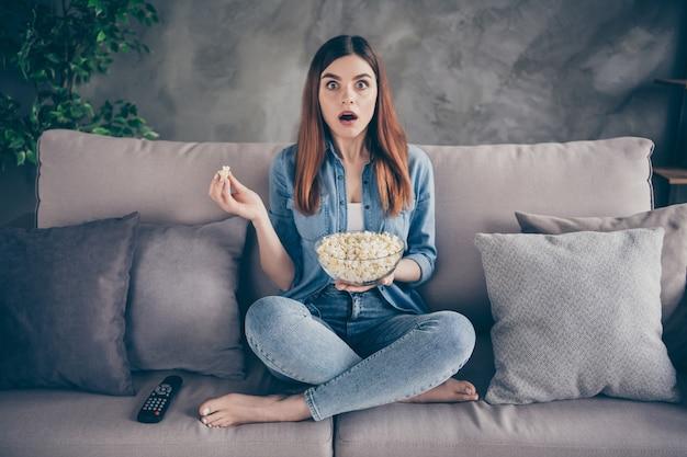 Szalona zszokowana pani siedzi na kanapie jeść pop kukurydzę oglądać thriller serial telewizyjny