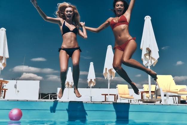 Szalone dziewczyny. dwie atrakcyjne młode kobiety w bikini trzymają się za ręce i mają otwarte usta podczas skakania w basenie na świeżym powietrzu