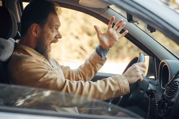 Szalony, agresywny kierowca krzyczy zirytowany ruchem drogowym