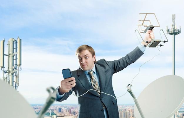 Szalony biznesmen z anteną i telefonem komórkowym próbuje złapać sygnał na dachu centrum biznesowego