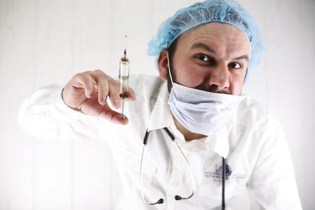 Szalony brodaty lekarz w białym fartuchu i starej strzykawce