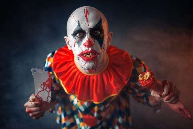 Szalony cholerny klaun z tasakiem do mięsa i ludzką ręką. mężczyzna z makijażem w kostiumie na halloween, szalony maniak, horror