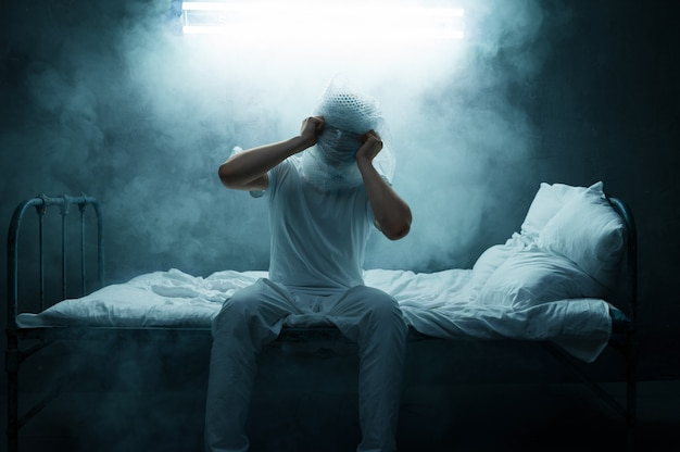 Szalony człowiek, bezsenność, ciemny zadymiony pokój. osoba psychodeliczna mająca problemy każdej nocy, depresja i stres, smutek, szpital psychiatryczny