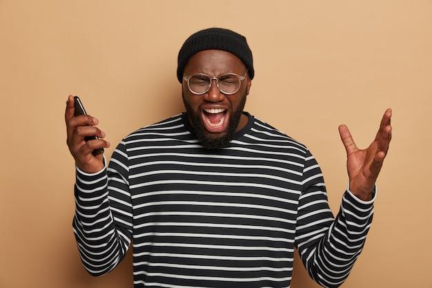 Szalony, emocjonalny ciemnoskóry mężczyzna krzyczy głośno, trzyma telefon komórkowy, podnosi ręce, otwiera usta