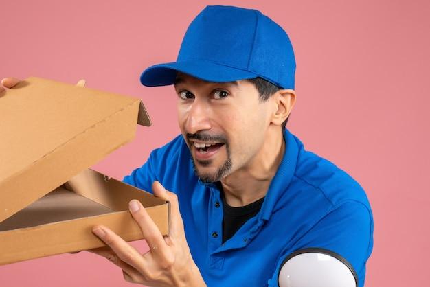 Szalony emocjonalny mężczyzna dostarczający w kapeluszu siedzący na zamówieniu otwierania skutera