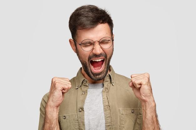 Szalony facet zaciska pięści i krzyczy ze złością, wyraża agresję i niezadowolenie