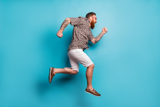 Szalony funky brodaty rudy facet podróżuje za granicę skacze