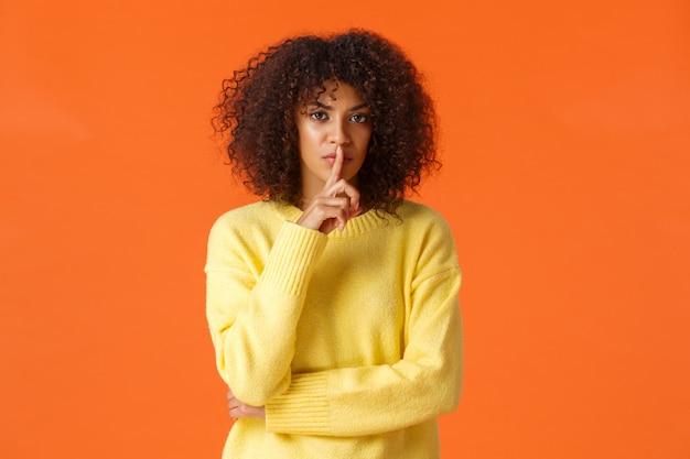 Szalony i niezadowolony, poważnie wyglądająca afroamerykańska kobieta mówiący w tajemnicy i prosząca przysięgę, że nie odzywa się słowami, przesuwając palec wskazujący wargami i wpatrując się w gniewny aparat, bądź cicho