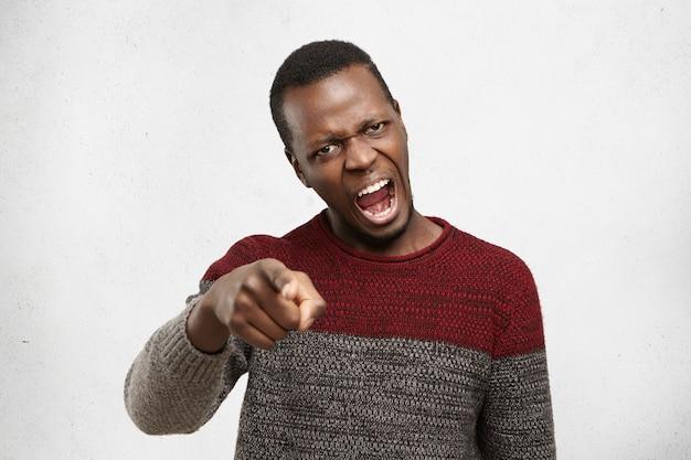 Szalony i wściekły afrio amerykanin krzyczy w gniewie i wściekłości, trzymając palec wskazujący. wściekły czarny mężczyzna w swetrze wrzeszczący z wściekłości, z czegoś niezadowolony