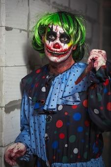 Szalony klaun z nożem na tle ceglanego muru. koncepcja halloween