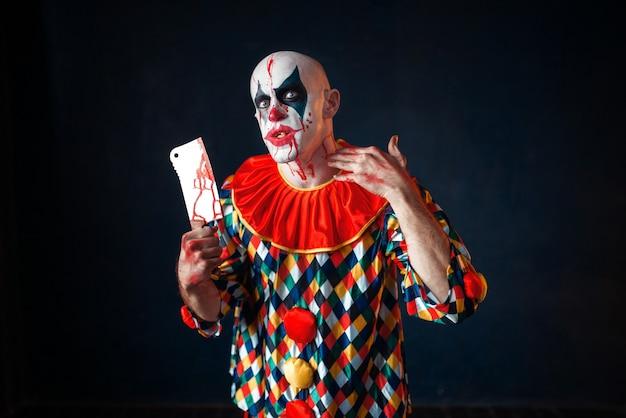 Szalony krwawy klaun z tasakiem do mięsa, cyrkowy horror. mężczyzna z makijażem w stroju karnawałowym, szalony maniak