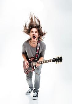 Szalony młody człowiek kręci głową i gra na gitarze elektrycznej na białym tle