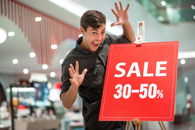 Szalony młody człowiek pozuje atakuje na czerwonym stojaku z napisem rabaty lokalizować w centrum handlowym.